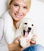 foto of long tongue  - Close up of woman in white sweater with white Labrador puppy sitting on her knees and yawning - JPG