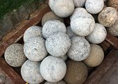 stock photo of cannonball  - Stone cannonball in wooden box in ancient fortress - JPG