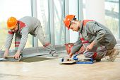 picture of trowel  - Two industrial tiler builder worker installing floor tile at repair renovation work - JPG