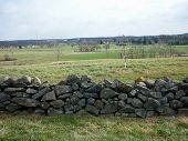 stock photo of battlefield  - A stone wall fence located in Gettysburg facing the battlefield - JPG
