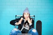 picture of hooligan  - Young hooligan hipster woman eating ice cream over blue brick wall - JPG