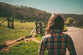 picture of cowgirl  - Young woman is walking around a ranch with cattle in the distance - JPG