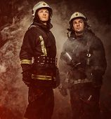 pic of firefighter  - Two firefighters with helmet and axe in a smoke - JPG