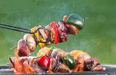foto of charcoal  - Meat and vegetable skewer on barbecue grill with fire - JPG