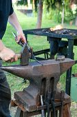 image of anvil  - Blacksmith working metal on the anvil in the outdoor workshop - JPG