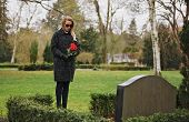 foto of grieving  - Young woman visiting a loved one at the cemetery paying respects with fresh rose flowers - JPG