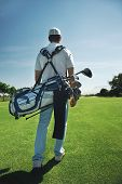 image of caddy  - Golf man walking with shoulder bag on course in fairway - JPG