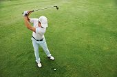 stock photo of striking  - High overhead angle view of golfer hitting golf ball on fairway green grass - JPG