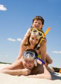 pic of summer beach  - Portrait of happy family in goggles and flippers lying on sandy beach against blue sky - JPG