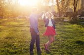 stock photo of jeans skirt  - loving couple dancing in the park at sunset - JPG