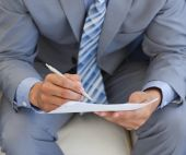 Close-up Of A Businessman Writing On A Paper