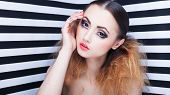 foto of ombres  - Graphic portrait of beautiful young woman with professional party make up false eyelashes on stripy background  - JPG
