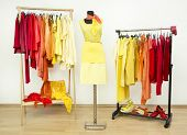 picture of dress mannequin  - Dressing closet with bright color coordinated clothes on racks and a yellow outfit on a mannequin - JPG