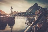 foto of reining  - Young travellers couple looking at sunset in Reine village - JPG