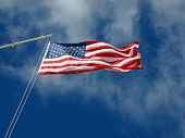 foto of wispy  - The American Flag Waving Before Wispy Clouds and a Blue Sky - JPG