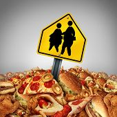 stock photo of obesity children  - Children diet problems and obesity crisis in the school concept as a heap of unhealthy fast food with two overweight fat kids on a a crossing traffic sign as a nutrition risk symbol for the youth - JPG