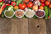foto of legume  - Legumes in bowls and vegetables on a wooden table - JPG