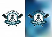 stock photo of shipbuilding  - International Shipbuilders emblems or logos with crossed oars behind a frame enclosing a ships anchor in blue on a white and mottled blue background - JPG