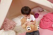 stock photo of teepee tent  - Toddler child kid engaged in pretend play with stuffed toys and teepee tent - JPG