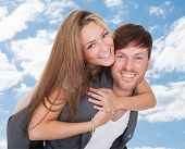 picture of piggyback ride  - Portrait of happy young man giving piggyback ride to girlfriend against sky - JPG
