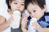 stock photo of mile  - Closeup portrait of happy Asian little boy and girl drink some mile from bottle on white background - JPG