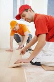 picture of carpenter  - Two parquet carpenter workers installing wood board during flooring work - JPG