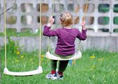 stock photo of swinger  - One girl play at rocker in backyard - JPG