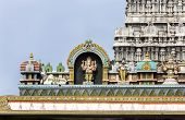 stock photo of glorious  - Ganesha Statue on glorious covered walkway with part of the eastern Gopuram of Annamalaiyar temple in background - JPG