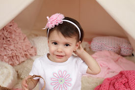 stock photo of toddlers tiaras  - Toddler child kid engaged in pretend play with a pink flower headband and teepee tent - JPG