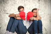 foto of broken hearted  - Young couple holding broken heart against grey background - JPG