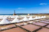 foto of salt mines  - salt piles in the saline of Janubio in Lanzarote with old toteen wind mill under blue sky - JPG