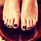 foto of black woman spa  - Beautiful women legs with black pedicure after Spa procedures  - JPG