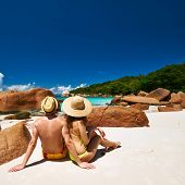 image of couple sitting beach  - Couple sitting on a tropical beach at Seychelles - JPG
