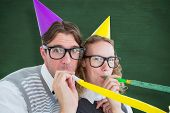 picture of blowing  - Geeky hipster couple blowing party horn against green chalkboard - JPG