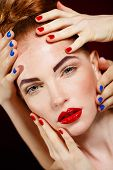 picture of freckle face  - Beautiful young model with red lips and red nail polish on a black background - JPG