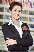 stock photo of receptionist  - Happy female receptionist worker standing at hotel counter - JPG