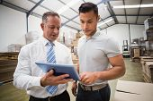 picture of warehouse  - Warehouse manager using tablet pc with colleague in a large warehouse - JPG