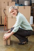 stock photo of pick up  - Smiling warehouse manager picking up cardboard box in a large warehouse - JPG