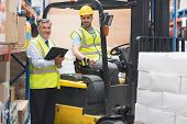 foto of forklift driver  - Driver operating forklift machine next to his manager in warehouse - JPG