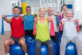 pic of senior class  - Portrait of happy people on fitness balls exercising with resistance bands in gym class - JPG