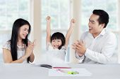 pic of applause  - Happy little girl finishing her homework and get applause from her parents at home - JPG