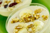 image of walnut  - Banana smoothie with sliced banana fruit and crushed walnuts on top