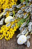 stock photo of mimosa  - French mimosa and catkins with easter eggs on wooden table - JPG