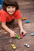 stock photo of little boys only  - Picture of little boy lying on the floor and playing with toy cars - JPG
