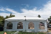 picture of canopy  - White canopy with four windows and a white picket fence in grass field - JPG