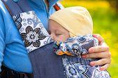 stock photo of sleeping  - Baby sleeping in sling outdoors - JPG