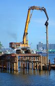 pic of hydraulics  - A hydraulic pile driver sinks a large support post into the river bed for bridge construction. The letters in the back say port. - JPG