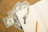 stock photo of memento  - Opened notebook with a blank sheet pencil key and money on the old tissue - JPG