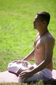 picture of pranayama  - Serene Indian young man in white pants practicing yoga on green grass in park doing Padmasana sitting with closed eyes in Lotus Pose breathing meditating relaxing full length vertical shot - JPG