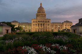 pic of cloudy  - The Capitol Building in Austin Texas with colorful flower beds in the foreground lit up by street lights as the sun sets and a cloudy sky grows dark as dusk. ** Note: Visible grain at 100%, best at smaller sizes - JPG